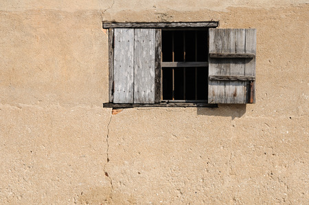 Old wooden window on wall in evening hour.