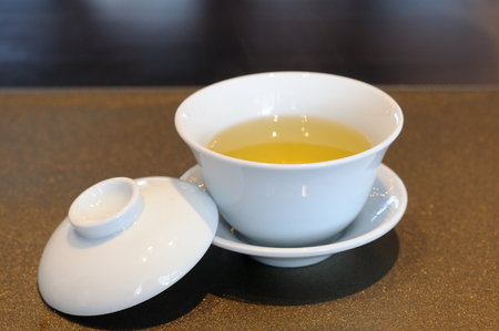 chinese tea cup: Chinese tea cup on luxury napery. Stock Photo