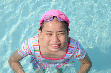 Asian girl stand in pool and looking up with smile  photo