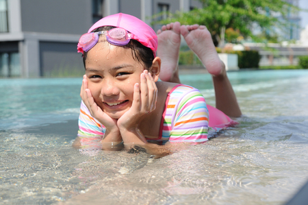 Asian girl lie prone and chin up in pool photo