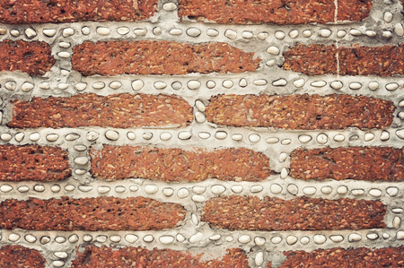 Red brick wall with small white rocks photo