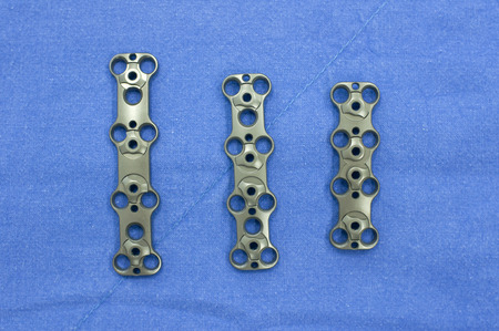 Bone plates 3 sizes on surgery cloth. Stock Photo