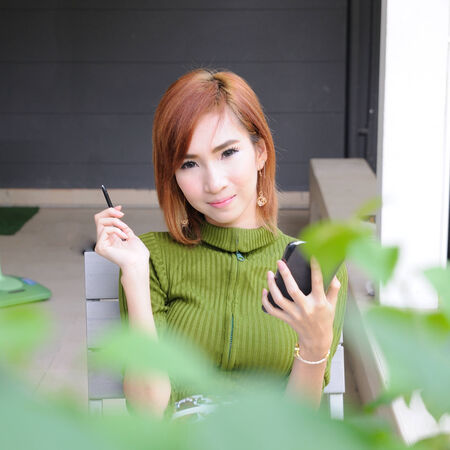 Asian woman using technology device in garden photo