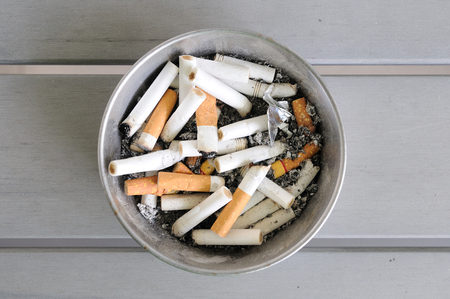 cigarettes in aluminium ashtray on wooden table. photo