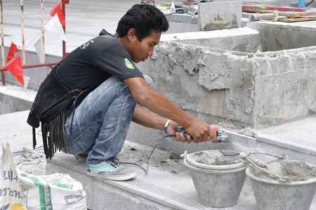 BANGKOK-OCTOBER 22: Unidentified man worker is cutting cement with handle grinder in front of building on October 22, Bangkok Thailand.