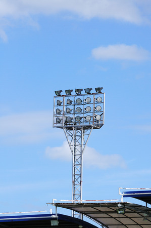 Single spot-light pole with blue sky in stadium photo