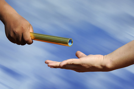 staffel: Relay-Athleten Hände Absenden Aktion mit Unschärfe blauen Himmel