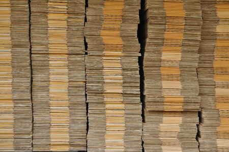 uitpakken: Veel uitpakken kartonnen doos stapelen op zwart pallet in de voorkant van het magazijn, voor web achtergrond.
