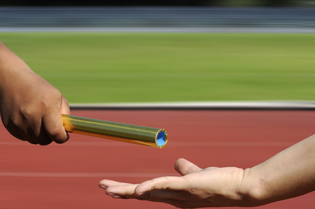 teammates: Relay-athletes hands sending action on blur race track, sport action.