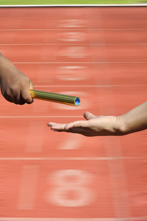 Relay-athletes hands sending action on blur race track  starting point, sport action.