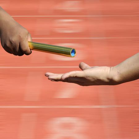 carrera de relevos: Relay-atletas manos envían acción en el punto de partida pista de carreras de desenfoque, la acción del deporte.