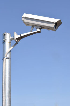 security monitor: White security camera monitor on iron pole.