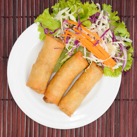 Fried spring rolls on white plate.