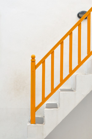 White vintage stairs with yellow banisters. photo