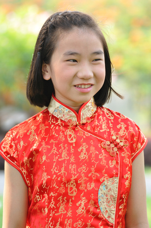 Asia female teenager wear red suit pose for take photo in garden, Chinese New Year traditions Stock Photo