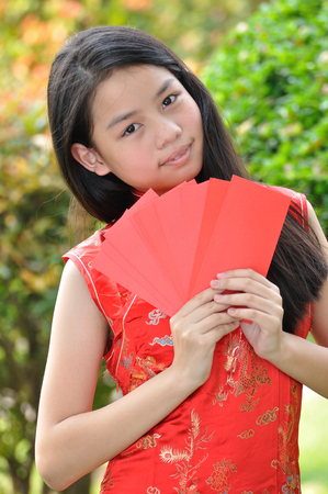 envelops: Asia female teenager show red envelops that have money in there (Ang Pao), Chinese New Year traditions