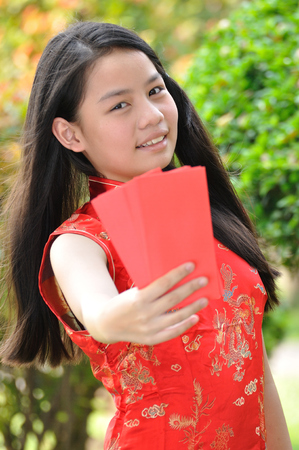 Asia female teenager show red envelops that have money in there (Ang Pao), Chinese New Year traditions photo
