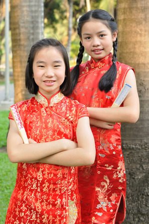 traditions: Asia female teenagers wear red suit pose for take photo in garden, Chinese New Year traditions