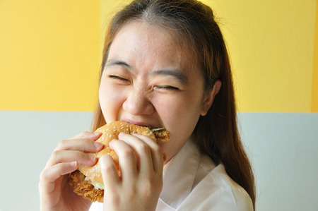 Asian woman age 28 years old in uniform eating chicken burger, junk food. photo