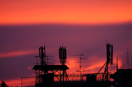 sattelite: Mobile 3G network pole on top building during sunset time