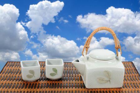 chinese tea pot: Chinese tea pot set on bamboo mat with blue sky. Stock Photo
