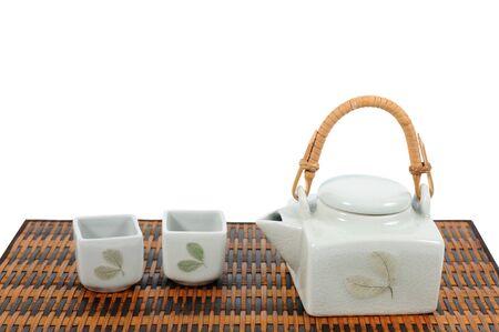 chinese tea pot: Chinese tea pot set on bamboo mat isolated on white background. Stock Photo