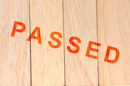 passed stamp: Light brown wood background with passed stamp.