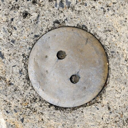 manhole cover: Manhole cover on street, top view.