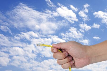 cat5: Man hand hold yellow cable with blue sky, business technology concept.
