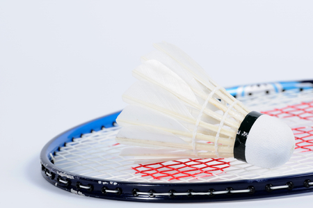 badminton racket: Single Shuttlecock lying on badminton racket.