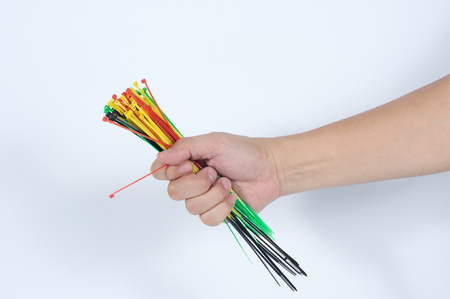 Man hand holding many color of cable ties.