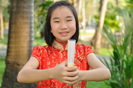 traditions: Asia female teenager wear red suit pose for take photo in garden, Chinese New Year traditions Stock Photo