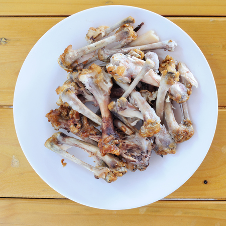 table scraps: Chicken bones in white plate on wooden table, food scraps Stock Photo