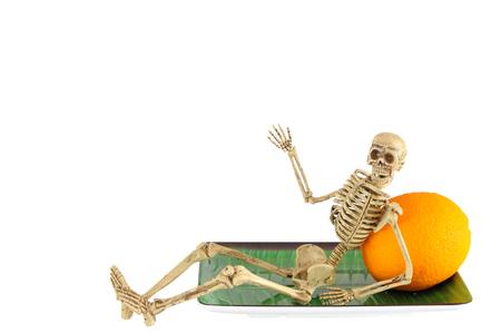 Human skeleton leaning on orange, relaxing
