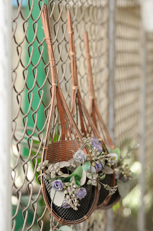 flower baskets: Dirty flower baskets with artificial flowers on wire wall Stock Photo