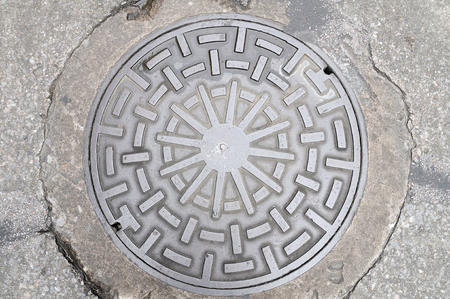 Manhole cover on street, drain cover top view.