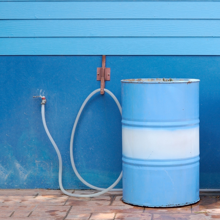Blue water tank parti-color and rubber tube with wooden wall Stock Photo