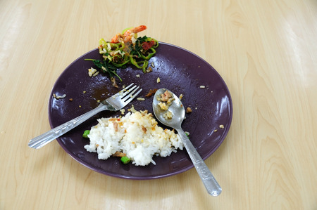 Food waste in plate on wooden table.