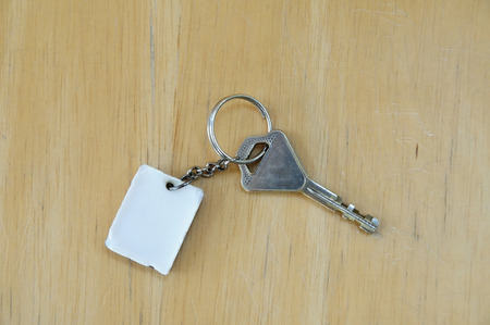 Single key with white key-chain on light wooden board Stock Photo