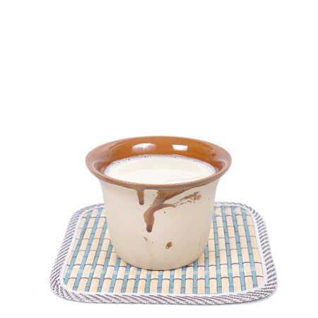 soymilk: Pottery cup of soybean milk lay on mat,