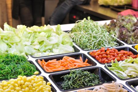 Various vegetables mixed on salad bar.