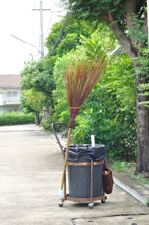 Garbage bin on wheel and broomstick