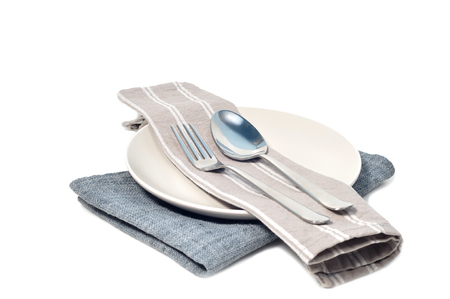 Gray napkin with stainless spoon and fork on white plate.