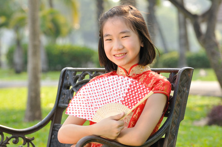 12 years old Asian girl in red Chinese new year Dress post profile in garden with red fan, fashion concept.