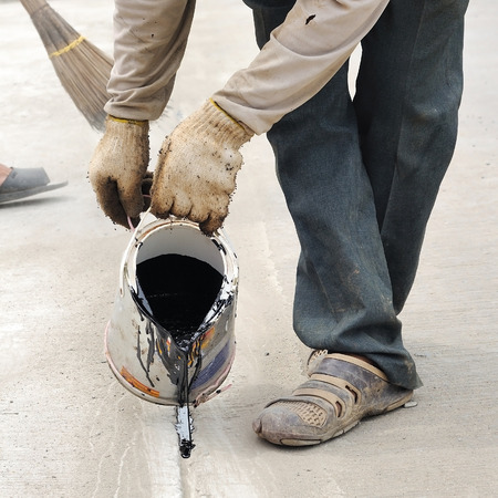 poured: Industrial worker poured asphalt liquid to make road line. Stock Photo
