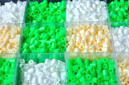 Green white cream perler beads for create bracelet papermarche Stock Photo