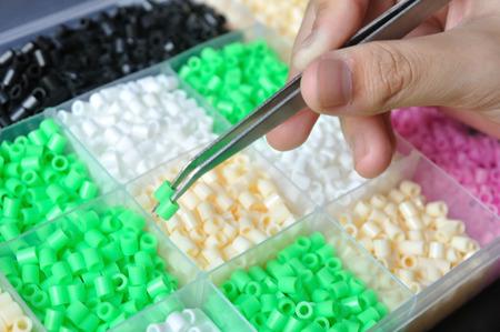 Girl hand use pincer catch green beads for create handmade work.
