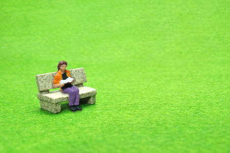 Selective focus miniature sitting on stone bench reading book, business concept.