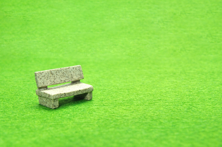 Selective focus miniature stone bench set on green yard. Imagens