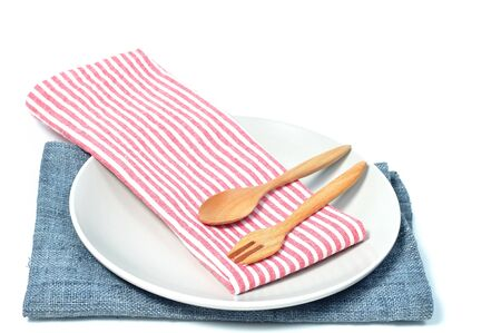Cycle plate lay on gray napkin and red strip napkin with wooden spoon and fork inside on white background.